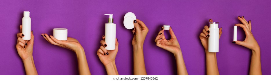 Female hands holding white cosmetics bottles - lotion, cream, serum on violet background. Banner. Skin care, pure beauty, body treatment concept.