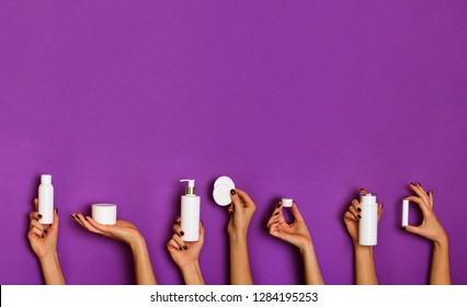 Female hands holding white cosmetics bottles - lotion, cream, serum on violet background. Square crop. Skin care, pure beauty, body treatment concept. Banner with copy space.