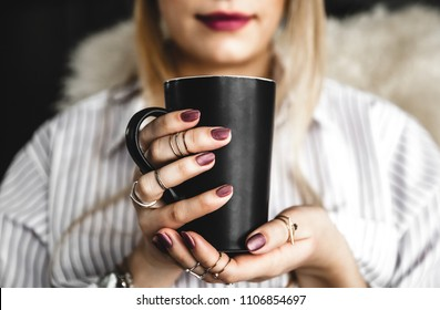 Female hands holding a white cup of tea, burgundy manicure, the girl is dressed in a shirt a