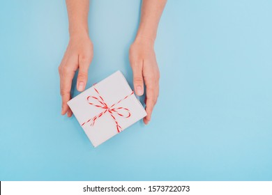 Female hands are holding a white gift box with a thin ribbon as a present for Christmas, New Year, Mother's Day or anniversary on a blue table background, top view. Place for text.