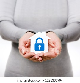Female hands holding white paper house with blue lock, family and real estate home security concept