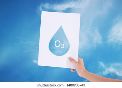Female hands holding white paper with water drop in blue sky background./Ozone concept