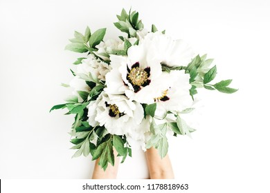 Female hands holding white peony flowers bouquet on white background. Flat lay, top view.