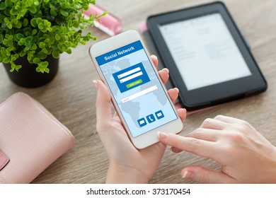 female hands holding white phone with social network on the screen and e-rider on the table