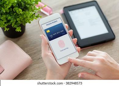 женские руки держат белый телефон с мобильным кошельком приложения на экране на женском столе