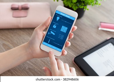 female hands holding white phone with app smart home on the screen on the women table
