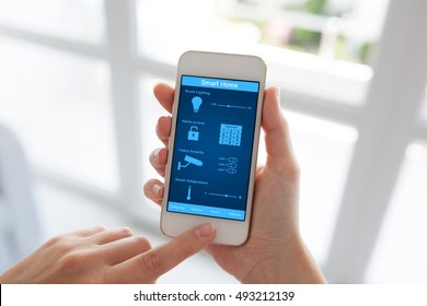 female hands holding white phone with smart home on screen against window