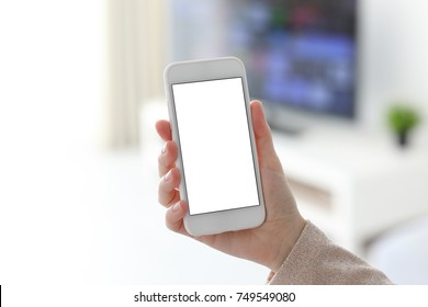 Female hands holding white phone with isolated screen in home room