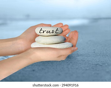 """Female hands holding white stack of pebbles with 'Trust""""' written on the top stone."""