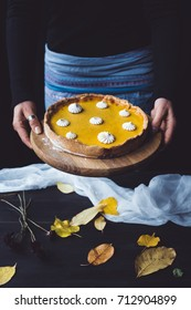 Female hands holding a wooden chopping block with pumpkin pie on it, over a table covered with autumn leaves