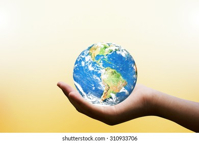 Female hands holding world on blurred sunset background with sun light. Elements of this image furnished by NASA