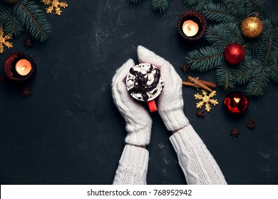 Female hands hot christmas beverage craft cup chocolate with marshmellow festive background with candles