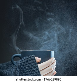 Female hands with a hot Cup of tea on a dark background.