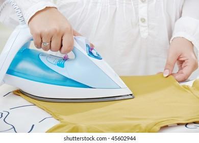 Female hands ironing t-shirt on ironing board.
