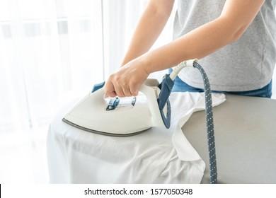 Female hands ironing white shirt on ironing board