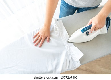 Female hands ironing white shirt collar on ironing board, view from above