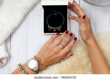 Female hands with jewelry and gift. Fashion accessories, wrist watches, glamor bracelets and rings