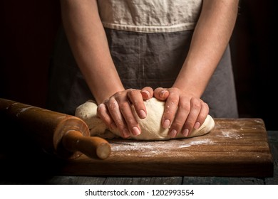 Female hands knead the dough on the table