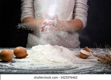 Female hands kneading dough for cooking bread, pizza or pasta. Cook clap hands with flour in the kitchen. Cloud of flour
