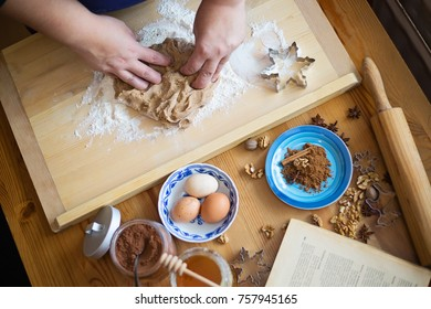 Female hands kneading a ginger bread dough on a wooden board, ingredients , roller and cooking book in front of her on the table