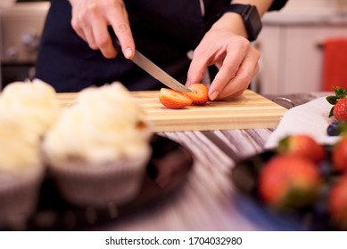 Female hands with a knife cut strawberries on a cutting board on the kitchen table. Cooking cupcakes with strawberries and blueberries.Selective focus.
