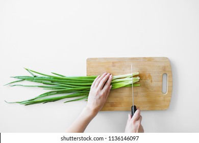Female hands with a knife, slicing vegetables on a wooden board on a white background.