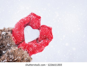 Female hands in knitted mittens with heart of snow in winter day. Love concept. Valentine day background.