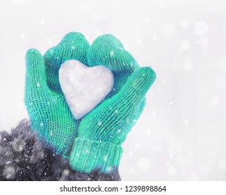Female hands in knitted mittens with heart of ice in winter day. Love concept. Valentine day background.