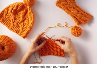 Female hands knitting with orange wool, on a white background, top view