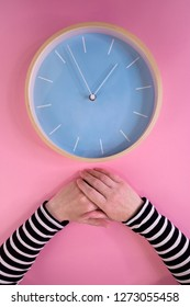 Female hands and large clock on pink background, maternal ageing and menopause, health care and illness prevention concept