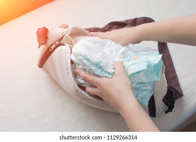 Female hands lay baby diapers in a bag, close-ups, diaper