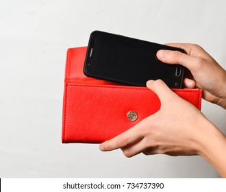 Female hands lay smartphone in red leather purse isolated on white background.