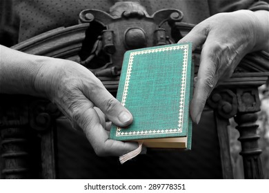 Female hands, leaning on a retro chair and holding a green book, black and white shot with green accent on the book