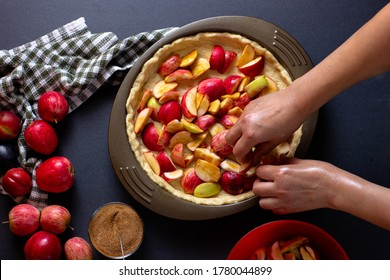 female hands make a yeast cake with apples and cinnamon in a shape