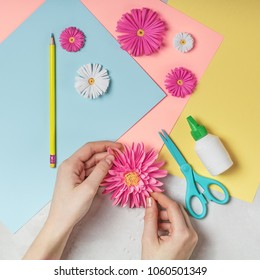 Female hands makes paper flower art. DIY concept. Pastel colors, flat lay.