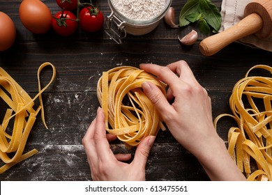 Female hands making fresh homemade pasta. Pasta ingredients on the dark wooden table top view.