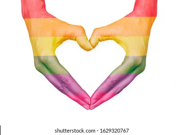 Female hands making a heart with LGBTQ+ raindow flag, can represent: health, love, caring, equality or beauty