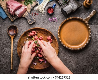 Female hands making minced meat stuffing on kitchen table background with  meat, force meat , meat grinder and spoon, top view. Cooking,recipes and eating concept