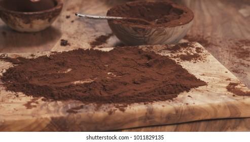 female hands making truffles in cocoa powder on board
