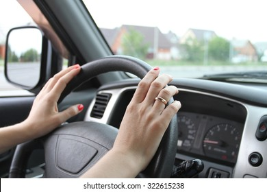 Female hands with manicure on a car wheel