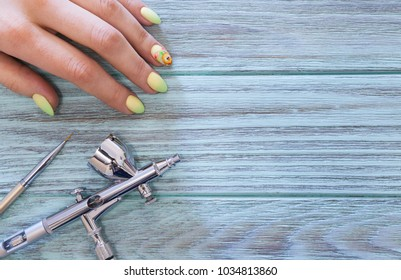 Female hands with a manicure on an Easter theme, an airbrush and a brush on a turquoise background.