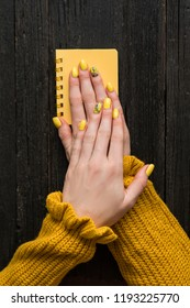 Female hands with a manicure on a yellow notepad. Top view