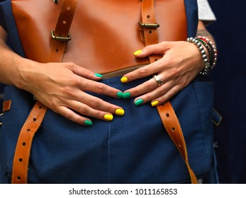 Female hands with manicured nails holding rucksack or bag in front of her
