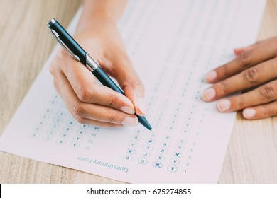 Female hands marking test answers with pen at desk