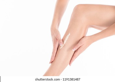 Female hands massage her leg with body lotion, close up, isolated on white. Applying cream is on the skin.