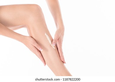 Female hands massage leg of woman with body lotion, close up, isolated on white. Applying cream is on the skin.