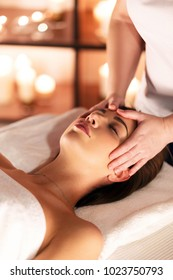 Female hands of masseuse doing massage on the head of beautiful young girl lying on massage table with closed eyes in a luxury spa resort