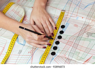female hands measuring distance with measuring tape and pencil on sewing pattern