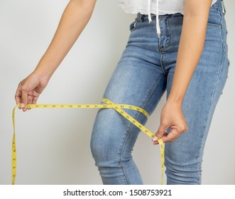 female hands measuring waist with measuring tape.
