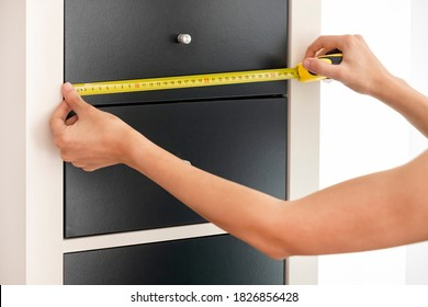 Female Hands Measuring The Width Of Drawers With An Automatic Tape Measure